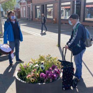Austausch auf Abstand: Horst-Wilhelm Bruhn (links) unterhält sich mit einem interessierten Bürger bei der Muttertagsaktion.