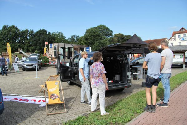 Autohändler beraten Kunden zum Thema Elektroautos.